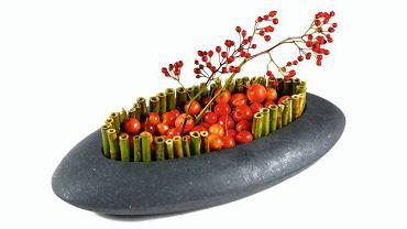 Japońskie natchnienie. I znów niewymuszona prostota - z czarnym naczyniem skontrastowano czerwonerajskie jabłka i owoce róży wielokwiatowej (Rosa multiflora). Brzegi 'wyrysowano' pociętym na kawałki pędami rdestu (najprościej umocować je w gąbce, którą wyłożono naczynie, lub połączyć drutem).