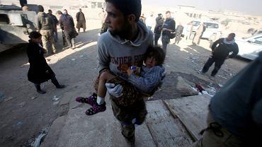 Mosul. Członek irackich sił specjalnych niesie dziewczynkę ranną w wyniku starć w mieście