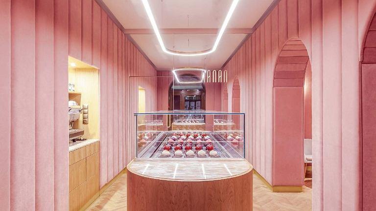 Wnętrze cukierni utrzymane jest w pudrowym, dymnym różu. Centralne miejsce zajmuje lada w kształcie eklerki.