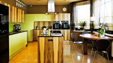 Wyspa kuchenna została tutaj pokryta drewnem limby o oryginalnym rysunku słojów - taki fornir zdobi fronty szafek.