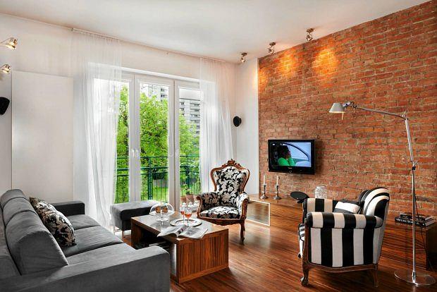 W pomieszczeniach często użytkowanych nie warto oszczędzać na podłogach. Zamiast malować ściany, usunięto z niej tynk.