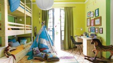 PO ZMIANIE. Do pokoju zamiast trzech oddzielnych łóżek, wprowadzono jedno trzypoziomowe. Dzięki temu na środku pokoju pozostało dużo wolnego miejsce do zabawy. Można na przykład ustawić namiot albo pobujać się na pięknym koniku na biegunach. Przez drzwi balkonowe wpada dużo światła. Zdobiące je zasłony są o kilka tonów ciemniejsze niż ściany.
