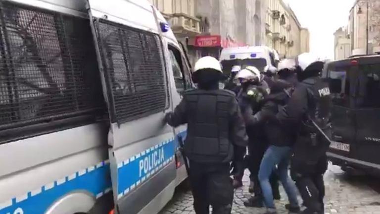 Kobieta doprowadzana przez policję do radiowozu