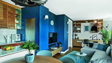 Granat nadaje charakter strefie wokół telewizora i powraca w innych pomieszczeniach w postaci dywaników, poduszek i detali. Część zabudowy przy kuchni wykończono boazerią z mdf pomalowaną na kolor ściany.