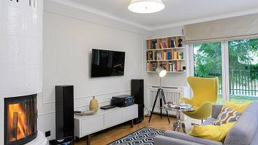 W EKLEKTYCZNYM SALONIE znalazło się miejsce zarówno dla metalowego stolika w stylu glamour, jak i prostej szafki z IKEA czy loftowej lampy stojącej. Nowoczesny grzejnik ukryto za estetyczną ażurową przesłoną.