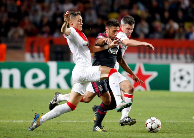 Benficas Eduardo Salvio forces his way past Monacos Lucas Ocampos and Jeremy Toulalan during their Champions League soccer match at the Louis II Stadium in Monaco
