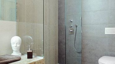 Coraz częściej zastępuje w naszych łazienkach standardową kabinę z brodzikiem. Za takim rozwiązaniem przemawia nie tylko estetyka, ale także wygoda. Zobaczcie przykłady.  <BR />ARANŻACJE WNĘTRZ - KABINY PRYSZNICOWE. Odpływ liniowy zamontowany przy ścianie wymaga spadku podłogi w jedną tylko stronę - w kierunku kratki (układanie płytek jest więc mniej kłopotliwe). Taka kabina jest idealna dla dzieci i osób starszych, bo eliminuje przypadkowe potknięcie się. Jeśli jest odpowiednio szeroka, może do niej wjechać nawet wózek inwalidzki. Fot. Sylwester Rejmer