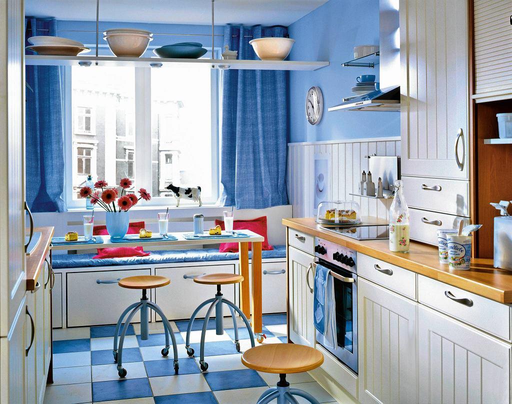 Do białych mebli kuchennych dobrano kolor niebieskie. Takie połączenie jest świeże i działa kojąco.