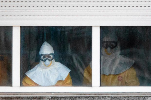 Pracownicy szpitala w kombinezonach ochronnych