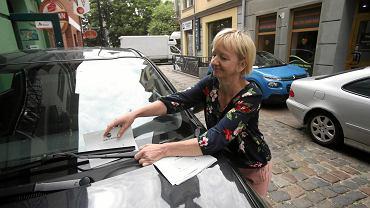 Małgorzata Zychowicz-Prus wsuwa kartkę z upomnieniem za wycieraczkę źle zaparkowanego samochodu
