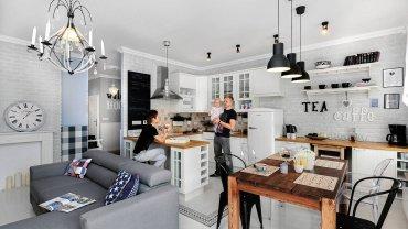 W kuchni, tak jak w połączonym z nią pokoju dziennym, umiejętnie zestawiono pozornie nieprzystające do siebie style. I tak np. skandynawska zabudowa kuchenna sąsiaduje z industrialnymi lampami i krzesłami. Uwagę zwracają wzorzyste płytki nad blatem - to ręcznie malowane wyroby z pracowni ceramicznej Artkafle. Resztę ścian obłożono białymi płytkami elewacyjnymi.