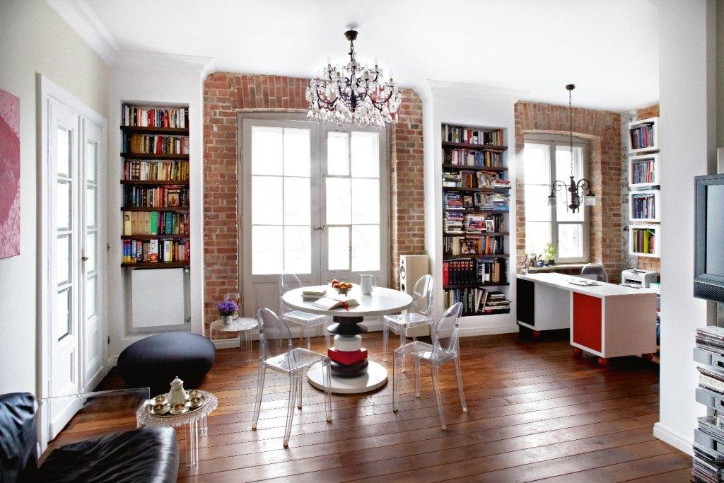 Lekkie, przezroczyste krzesła i stoliki, kanapa bez bocznych oparć, regały na książki we wnękach ściennych - mebli jest sporo, a jakby ich nie było.
