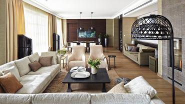 Salon to przestrzeń do słuchania muzyki - między oknami stanęły głośniki marki Wilson przypominające stylowe sekretery. Kanapy są z B&B Italia, fotele z Maxalto, a lampa stojąca z Moooi. Obudowę kominka zrobiła firma Benetti Stone z ryflowanego kamienia. Fakturą nawiązuje do niej fornir ściany z akwarium.