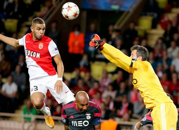 Monacos Layvin Kurzawa challenges Benficas goalkeeper Arthur during their Champions League soccer match at the Louis II Stadium in Monaco