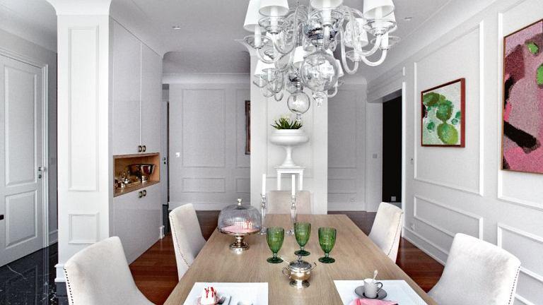 Jadalnia i kuchnia otwierają się na siebie. Stół Paola z blatem z bielonego dębu, krzesła Sophie, żyrandol Egmont, symetrycznie wiszące lampy nad stołem, w głębi na postumencie donica Deauville (BBHome).