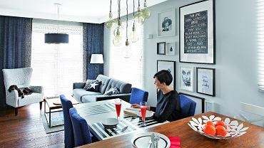 Spory stół (ze sklepu Take me Home) ztapicerowanymi krzesłami (domartstyl.eu) przystawiono do wyspy. Ewa i Marek bardzo sobie chwalą to rozwiązanie, bo przygotowując posiłek dla gości, nie czują się wyłączeni zżycia towarzyskiego. Ozdobą tej części pomieszczenia jest galeria grafik, zdjęć iplakatów oprawionych wbiałe iczarne ramki. Nad stołem - siedem lamp-żarówek (bylight.pl).