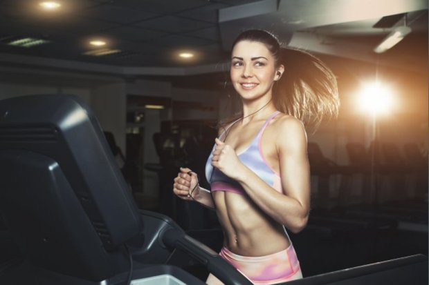 RYoung sporty woman running on machine in the gym and listening music in headphones8BIM8BIMC%#