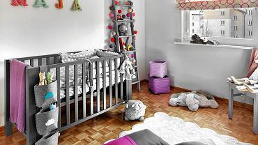 Mama Mai jako osoba praktyczna uważa, że pokój dla niemowlaka urządza się nie na rok czy dwa lata. Dlatego wybrano meble, które posłużą znacznie dłużej, a wesoły, ciepły klimat stworzono tańszymi dodatkami i ozdobami. <BR />WNĘTRZA - METAMORFOZY. Pokoik poweselał i odmłodniał, gdy pojawiły się dodatki w odcieniach różu i fioletu - barw ładnie komponujących się z szarością. Równie radosny jest wzór groszków, który stał się motywem przewodnim wystroju. Widnieje na rolecie, pościeli, dywanie oraz (bardzo delikatny) na tapecie, którą oklejono ścianę  za łóżeczkiem.