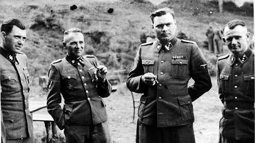 Od lewej: Dr Josef Mengele (1911-79), zwany Aniołem Śmierci, lekarz SS, który w Auschwitz zasłynął z selekcji więźniów przeznaczonych do natychmiastowego zabicia oraz powolnego uśmiercenia przez pracę, a także dokonywał na nich pseudonaukowych eksperymentów. Po wojnie żył spokojnie w Brazylii; Rudolf Höss (1900-47), komendant Auschwitz-Birkenau; Josef Kramer (1906-1945), komendant obozów Natzweiler-Struthof, Auschwitz II-Birkenau i Bergen-Belsen; oraz N.N.