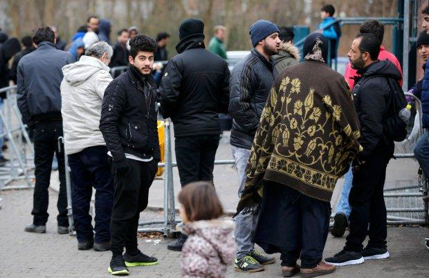 Migranci czekają na rejestrację przed Biurem do spraw Uchodźców i Migrantów w Berlinie