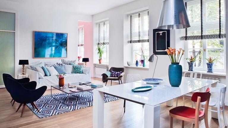 Marmurowy blat stołu Dolmen marki Poliform wsparty jest na masywnych nogach. Nad stołem lampa KTribe S firmy Flos. Krzesło z czerwonym siedziskiem Basel Chair to odświeżona przez projektantów Vitry tradycyjna forma. Na podłodze naturalny, rodzimy dąb.