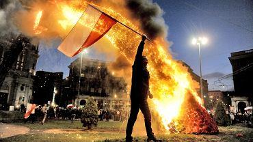 """Demonstrant z polską flagą na pl. Zbawiciela. W tle płonąca tęcza. Ponad 1000 osób opublikowało to zdjęcie na Facebooku. Zarówno ci oburzeni spaleniem tęczy na pl. Zbawiciela, jak i fani profilu """"Płoń tęczo płoń"""". Jedni z oburzeniem komentują zniszczenie instalacji, drudzy cieszą się z jej spalenia. Jedni i drudzy uznali zdjęcie za ważne. Mimo zapewnień organizatorów Marszu Niepodległości, w czasie demonstracji znów doszło do bijatyk i przepychanek. Spalona została tęcza na pl. Zbawiciela, w stronę ambasady Rosji poleciały race i butelki z benzyną. Grupa, które odłączyła się od marszu, wtargnęła na teren squatów przy ul. ks. Skorupki i ul. Wilczej - Przychodnia i Syrena. Po tych atakach ratusz postanowił rozwiązać marsz"""