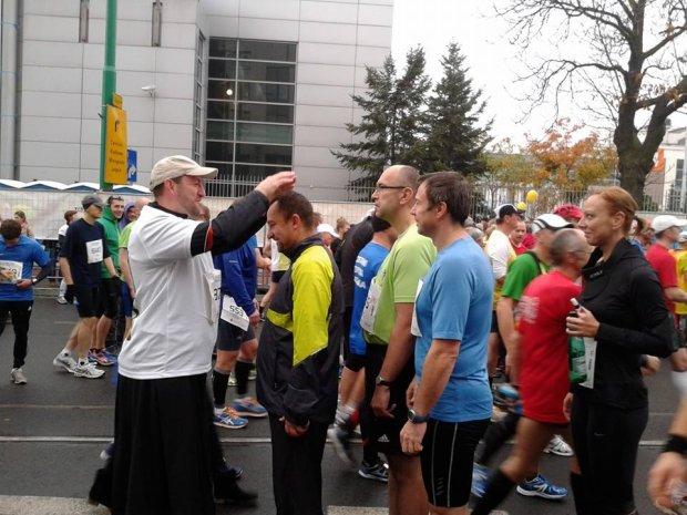 Ksiądz Adam Pawłowski przed maratonem udziela błogosławieństwa biegaczom