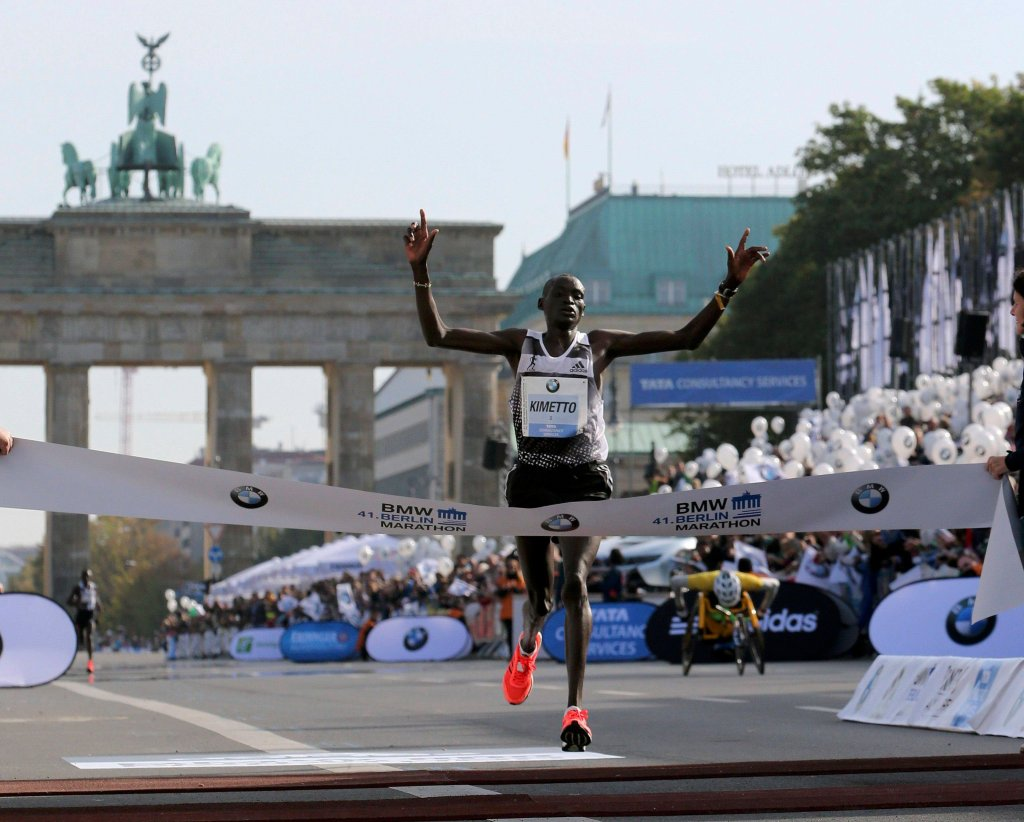 aKimetto of Kenya crosses the finish line in new world record time to win the 41st Berlin marathon