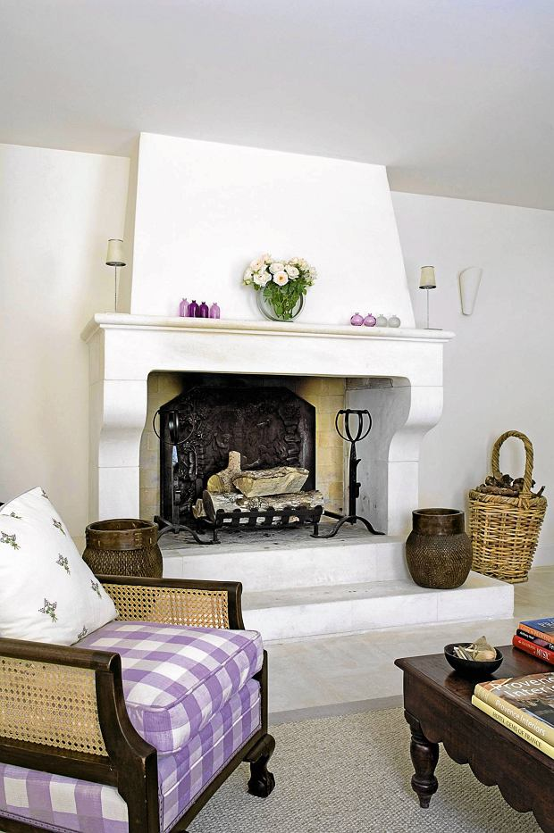Provencal holiday house with courtyard garden SLOWA KLUCZOWE: day colour interior living room white chair fresh coffee table purple cushion fireplace hearth mantlepiece log basket firewood rural urn chimneybreast lilac detail furniture seating