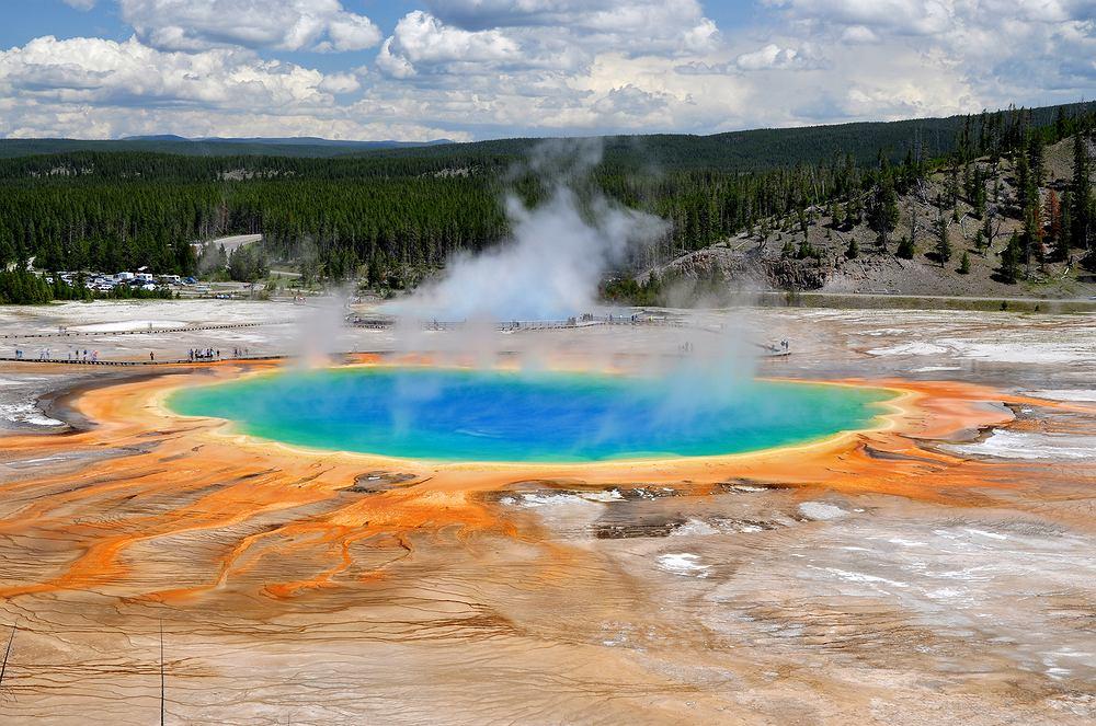 Grand Prismatic Spring w Yellowstone Park. Grand Prismatic Spring w Yellowstone Park to największe w Stanach Zjednoczonych, a trzecie na świecie gorące źródło. Ma 75 metrów szerokości, 91 długości i 49 głębokości. W ciągu minuty wylewa około 2 tysięcy litrów wody o temperaturze 71 stopni Celsjusza. Zachwycają jego odblaskowe kolory, które są przede wszystkim zasługą bakterii oraz alg osadzających się na krawędzi zbiornika.