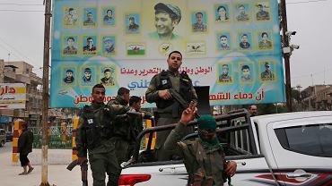 Członkowie kurdyjskich sił bezpieczeństwa wewnętrznego stoją przed gigantycznym plakatem przedstawiającym portrety bojowników zabitych w walce przeciwko bojownikom ISIS, Manbij, północna Syria, 28 marca 2018 r.