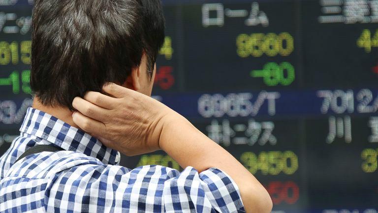 Człowiek patrzący na notowania giełdowe w Tokio