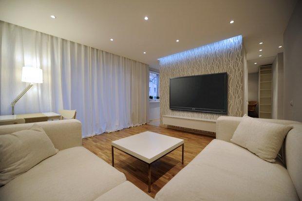 Jasny i nowoczesny salon zyskał efektowną, podświetlaną ścianę, na której zawieszono telewizor.