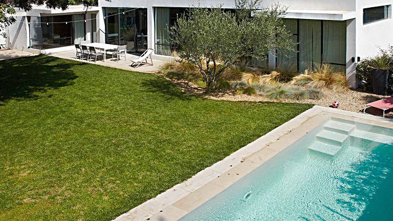 Wokół domu rozległy ogród z basenem i odpornymi na upały roślinami.