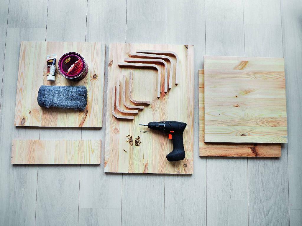 Robimy stolik krok po kroku. Potrzebne są: . deski sosnowe: 33 x 40 cm (blat), 31 x 40 cm (półka), 10 x 40 cm (łącznik blatu z półką), 60 x 40 cm (bok); 38 x 40 cm (podstawa)  . wsporniki drewniane gięte: 20 x 21 cm/4 szt., 11 x 15 cm/4 szt. . wkręty do drewna . wkrętarko-wiertarka z wiertłami . wosk do drewna . wełna stalowa