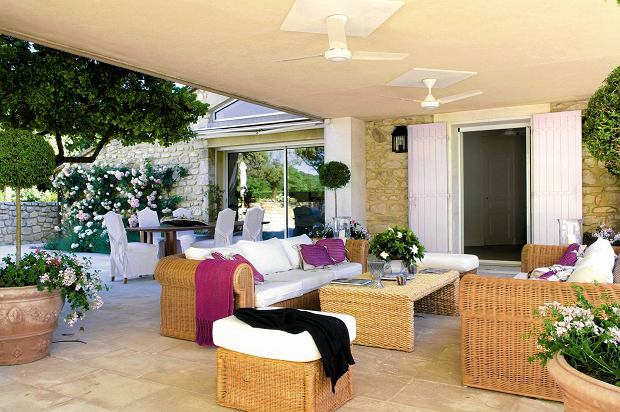Provencal holiday house with courtyard garden SLOWA KLUCZOWE: day colour exterior patio terrace cane furniture outdoor furniture coffee table plant pot climbing plant slip cover table open double door ceiling fan topiary overview furniture outside outdoors
