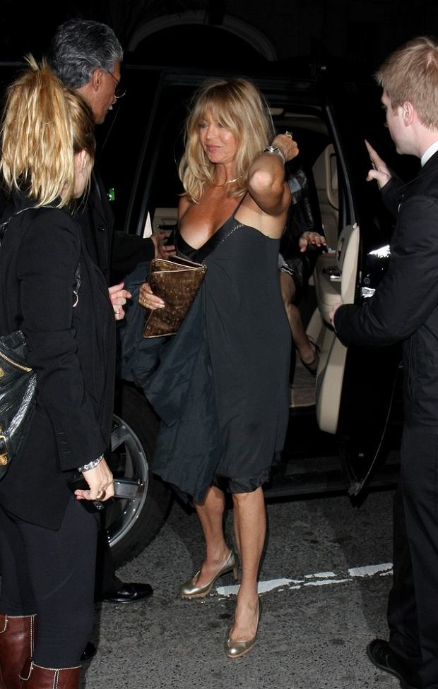 Goldie Hawn is seen exiting a vehicle while the straps fall from her dress in New York City, revealing more than she intended. Her driver and assistant quickly point out her slip, and she puts the straps back onto her shoulders with a big smile.  Pictured: Goldie Hawn  Ref: SPL97942  020509   Picture by: Steffman / Curd / Splash News     World Rights