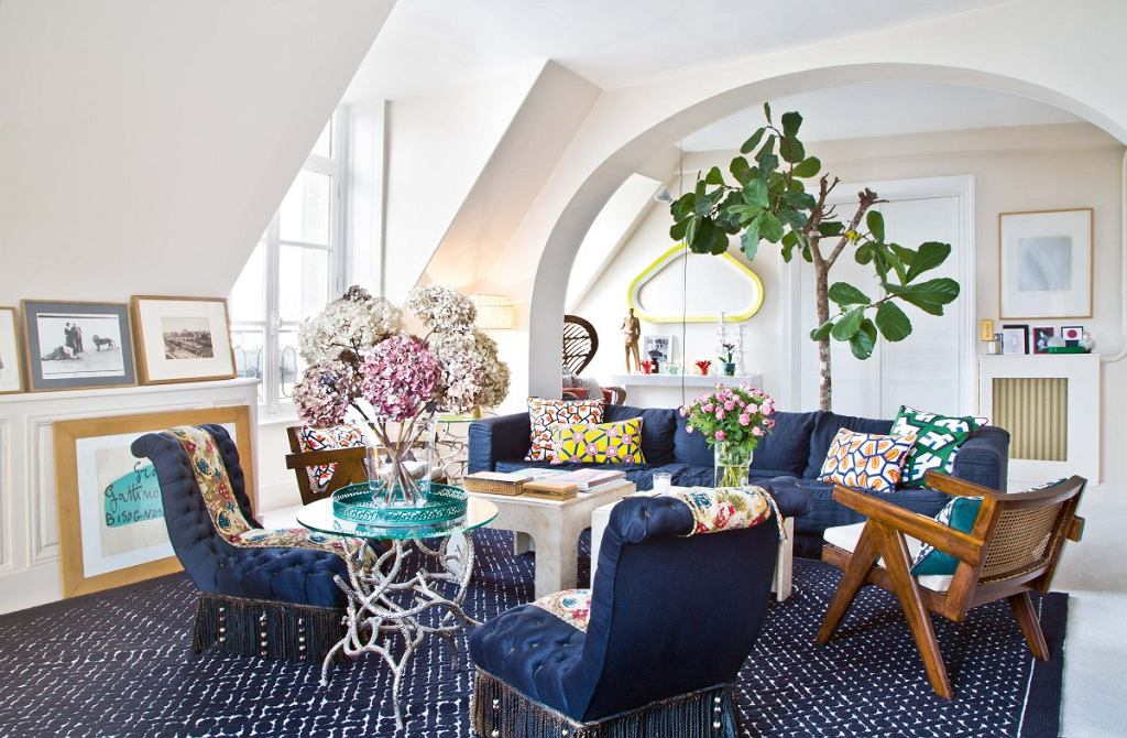Wsalonie dekoratorka zestawiła ozdobione frędzlami pikowane fotele, kolonialne siedziska, oryginalne stoliki kawowe (jeden znich - betonowy) iwspółczesną kanapę.