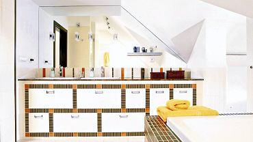 Drobnymi kafelkami obramowano szafki w tej jasnej łazience. Powstały w ten sposób graficzny wzór to ważny element aranżacji.