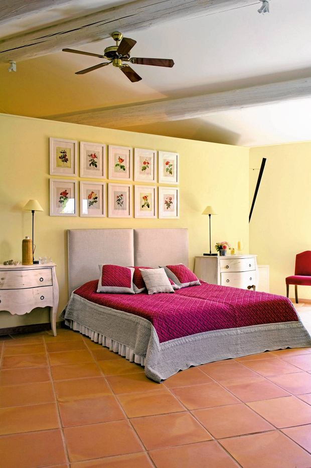 Provencal holiday house with courtyard garden SLOWA KLUCZOWE: day colour interior flooring bedroom bed wooden wooden floor double bed bed cover pink ceiling fan chest of drawers artwork botany tiled floor partition beamed ceiling overview contrasting colours room indoors inside bedding