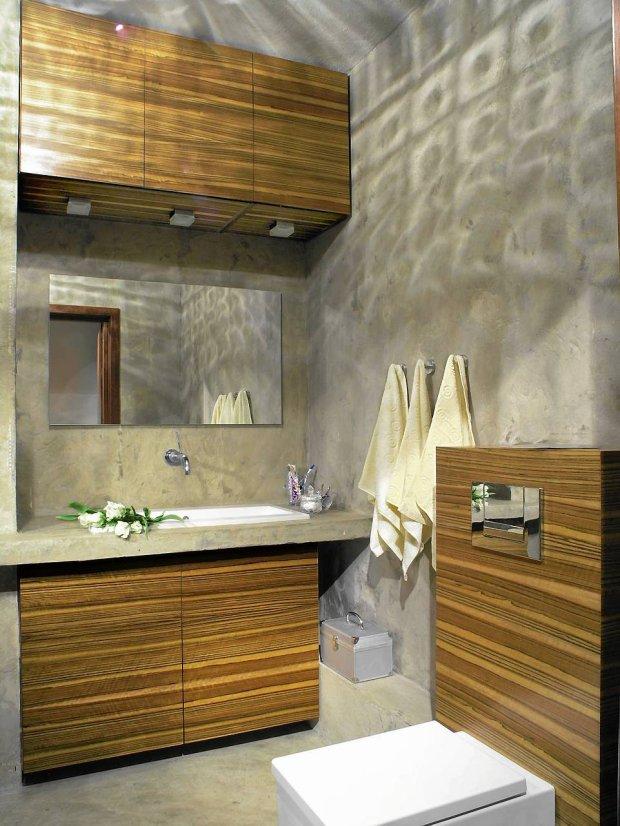Łazienka ze ścianami pokrytymi betonem.