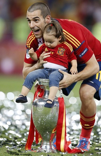 Spain's Alvaro Negredo and a child celebrate with the trophy after defeating Italy to win the Euro 2012 final soccer match at the Olympic stadium in Kiev, July 1, 2012.                 REUTERS/Alessandro Bianchi (UKRAINE  - Tags: SPORT SOCCER)