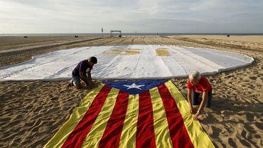 Plaża El Masnou w pobliżu Barcelony. Zwolennicy niepodległej Katalonii rozwijają regionalną flagę, szykując demonstrację poparcia dla swego separatystycznego rządu. W głębi napis 'Si' (tak) - dla referendum niepodległościowego.