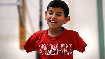 Syryjski uchodźca Ahmad Alkhalaf, który stracił ręce w wyniku wybuchu bomby, bawi się w obozie dla uchodźców.