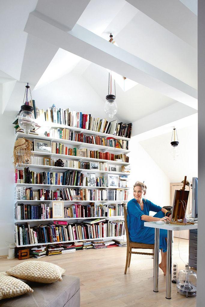 Kostiumografka w swojej pracowni. Biblioteka służy nie tylko do przechowywania książek, ale również do eksponowania rodzinnych fotografii.