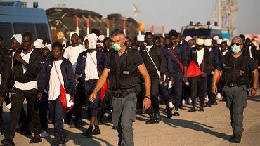 Imigranci są eskortowani przez włoską straż graniczną do punktu relokacji, port Augusto na Sycylii, 23 czerwca 2017.