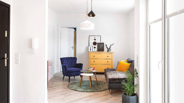 Ten widok pokoju dziennego nie zapowiada jeszcze feerii kolorów. Chyba że zajrzymy za ściankę, na której wisi domofon (po drugiej stronie stoi czerwona szafka). Albo uchylimy drzwi do sypialni pomalowanej na kobaltowy kolor.