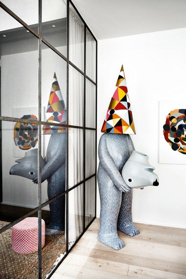 Przy szklanej �cianie pomi�dzy salonem a sypialni� ? bezg�owy nied�wied� ameryka�skiego artysty Richarda Colmana. Prace kolekcjonowane przez gospodarzy ��czy wyraz groteski i kolorystyka ? czapka arlekina nawi�zuje do tonacji obrazu Geoffa McFetridge?a.
