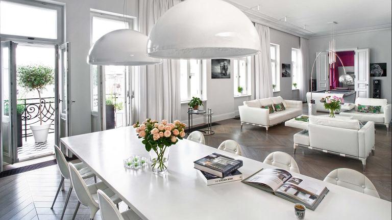 Sofa i fotele Prive (Cassina) zaprojektowane przez Philippe'a Starcka; stoliki kawowe Raymond (Minotti), lampa stojąca Arco (Flos) projektu braci Castiglioni. Pod oknem stolik Adjustable Table E1027 (ClassiCon) projektu Eileen Gray. Z prawej w głębi - kino domowe.
