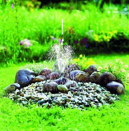 Prostota i minimalizm. Ukryta w zakopanym w ziemi pojemniku z wodą pompka tłoczy ją do dyszy wystającej z małegho kopczyka z kamieni.